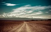 stock photo of pastures  - Empty rural road going through prairie under cloudy sky in Charyn canyon - JPG