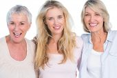 stock photo of grandmother  - Three generations of  cheerful women smiling at camera on white background - JPG