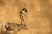 stock photo of dizzy  - acrophobia woman tall stands on top of a rock cliff edge and is fearful horror - JPG
