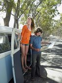 stock photo of campervan  - Full length of happy young woman standing in campervan door with man looking at map during road trip - JPG