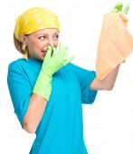 Young woman as a cleaning maid holding rag and pinching her nose because of bad smell, isolated over