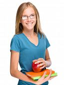 picture of skinny girl  - Young skinny student girl is holding exercise books and apple - JPG