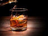 stock photo of whiskey  - Pouring whiskey drink into glass - JPG