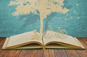 stock photo of cutting trees  - Paper cut of children read a book under tree on old book - JPG