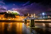image of mozart  - Night view of Salzburg with castle in background and Mozart bridge over Salzach river in foreground - JPG