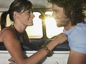 stock photo of campervan  - Side view of romantic young couple looking at each other in campervan - JPG