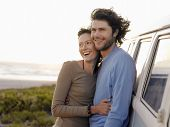 foto of campervan  - Smiling young couple embracing by campervan on beach - JPG
