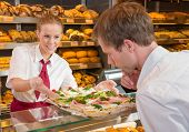 image of trays  - Salewoman or shopkeeper in bakery presenting tray with sandwiches to customer - JPG