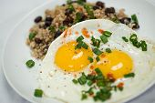stock photo of scallion  - Beautifully plated breakfast featuring 2 eggs served sunny side up over brown rice and black beans - JPG