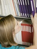 picture of shelving unit  - Closeup of a female college student selecting book from shelf in library - JPG