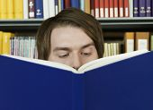 picture of shelving unit  - Closeup portrait of a young man reading a book in library - JPG