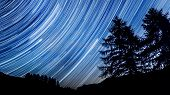 stock photo of meteor  - Star trail effect over mountain and trees in night sky - JPG