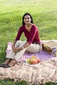 Mid-adult Indian woman sitting on picnic blanket