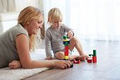 foto of indoor games  - Mother with a child playing with wooden blocks at home - JPG