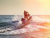 foto of water jet  - Silhouette of strong man jumps on the jetski above the water at sunset - JPG
