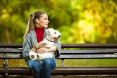 picture of maltese  - young woman hugging a maltese dog out in the park - JPG
