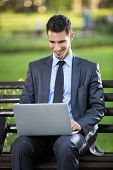 stock photo of work bench  - Businessman sitting on bench with laptop in park - JPG