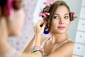 stock photo of hair curlers  - Young  girl with hair curlers in hair standing front  the mirror puts earring - JPG