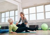 foto of personal assistant  - Female trainer helping old woman getting up from a exercise mat at gym - JPG