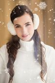 stock photo of muffs  - Pretty brunette with ear muffs smiling at camera against snow falling - JPG