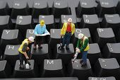 picture of figurine  - Miniature construction workers repairing a computer keyboard - JPG