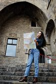 image of gothic female  - Beautiful tourist woman on vacation with a map in antique gothic city young traveler girl searching right direction on city map pretty young female tourist studying a map standing in gothic quarter - JPG