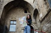 picture of gothic female  - Charming tourist woman studying a map standing in gothic quarter in Barcelona pretty young tourist girl holding city map in the hands smiling female traveler searching right direction on city map - JPG