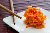 image of fermentation  - small serving of fermented carrots served on a small white plate with chop sticks