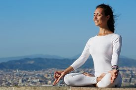 pic of yoga  - Yoga on high altitude with big city on background smiling woman seated in yoga pose on amazing city background woman meditating yoga and enjoying sunny evening woman makes yoga on mountain hill - JPG