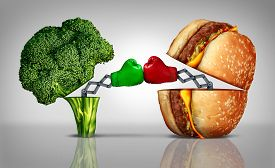 stock photo of boxing  - Food fight nutrition concept as a fresh healthy broccoli fighting an unhealthy cheese burger with boxing gloves emerging out of the meal options punching each other - JPG