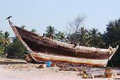 foto of old boat  - The old wooden fishing boat is on the sand beach - JPG