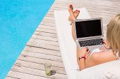 picture of swimming  - Woman working with laptop computer by the swimming pool - JPG