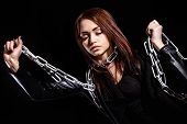 foto of low-necked  - Beautiful young woman with chains over black background - JPG