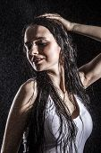 picture of dancing rain  - Sexy young woman dancing under the rain over black background - JPG
