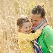 foto of bonding  - Caucasian mother and daughter hugging smiling and sharing a tender bonding moment amongst meadow grass - JPG