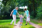image of children walking  - Happy active woman enjoying hiking with two children school age boy and cute curly toddler girl walking together in a beautiful pine wood forest on a sunny summer day - JPG