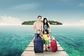 stock photo of carry-on luggage  - Portrait of attractive family arriving at resort and standing at resort bridge with their luggage - JPG
