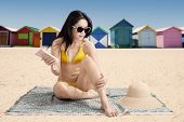 pic of suntanning  - Young asian lady wearing swimsuit while sitting at beach and using suntan lotion with the background of the beach cottage - JPG