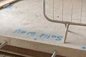 pic of slab  - A written note saying solid wall sprayed on a concrete slab on a a construction site - JPG