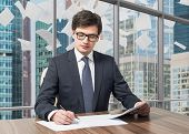 foto of diligent  - Handsome legal consultant is dealing with due diligence process in a modern skyscraper office with a panoramic Moscow city view. Pages of contract are falling down from the sky. ** Note: Shallow depth of field - JPG