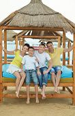 foto of lunch  - Portrait of a happy family having lunch on beach - JPG