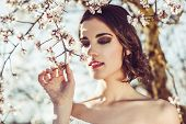 stock photo of flower girl  - Portrait of young woman in the flowered garden in the spring time - JPG