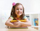 foto of preschool  - Cute kid girl preschooler with books indoor - JPG