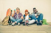 stock photo of addict  - Group of friends of different ethnics sitting on the street and looking at mobile phone  - JPG
