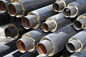 stock photo of insulator  - Steel pipe with heat insulation on construction site - JPG