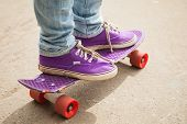stock photo of skate board  - Young skateboarder in gumshoes and jeans standing on his skate - JPG