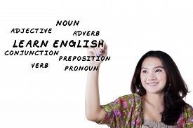 image of verbs  - Portrait of lovely female high school student writes English materials on whiteboard - JPG