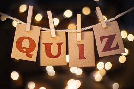 picture of quiz  - The word QUIZ printed on clothespin clipped cards in front of defocused glowing lights - JPG