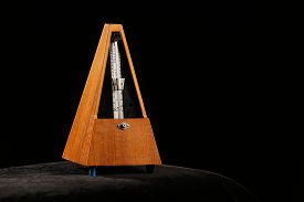pic of pendulum  - Mechanical metronome giving tact by ticking certain beats per minute with pendulum swing - JPG