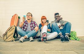stock photo of addicted  - Group of friends of different ethnics sitting on the street and looking at mobile phone  - JPG
